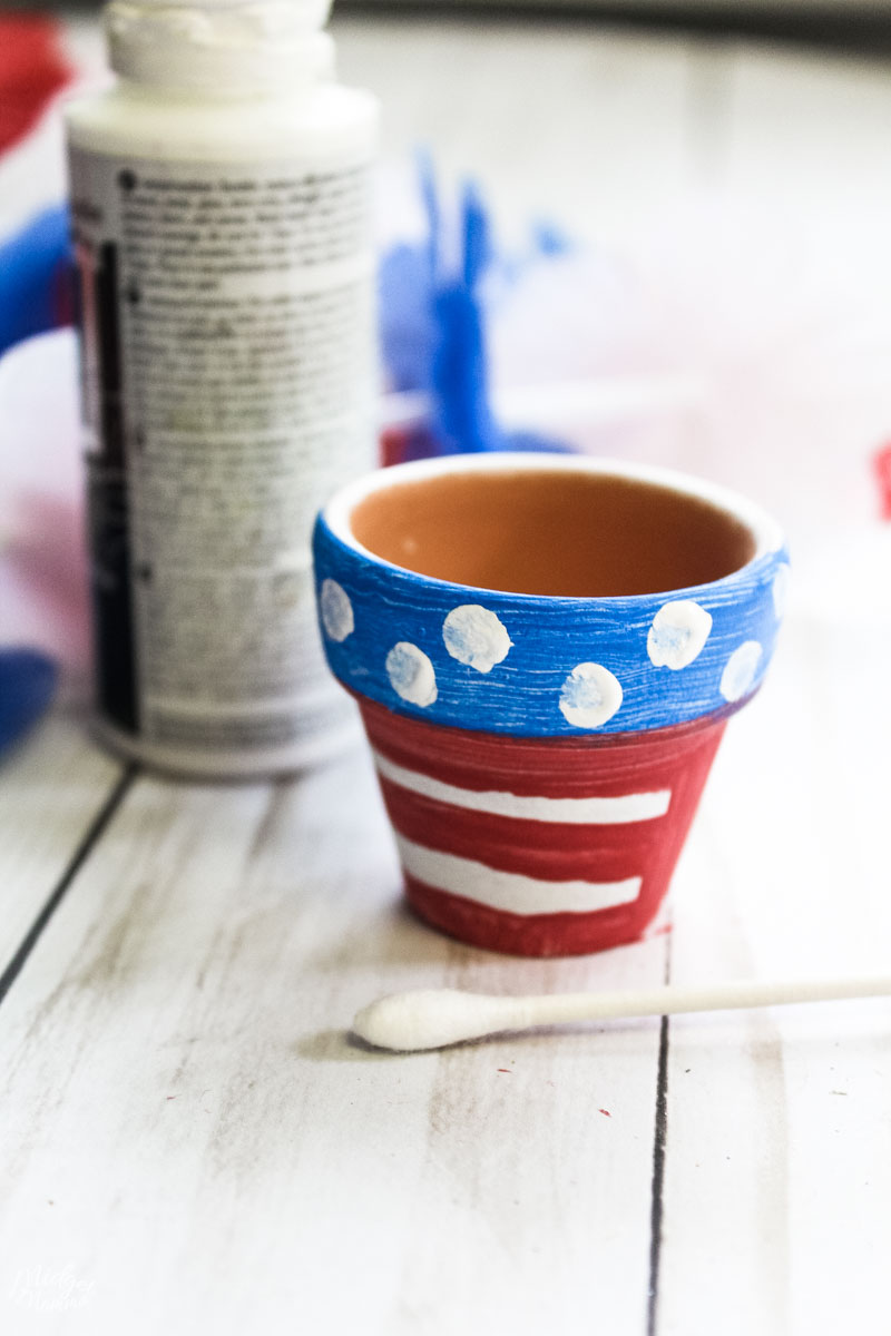 terra cotta pot painted with red and white stripes, with a thick blue stripe and white dots added by using a Qtip and white craft paint.